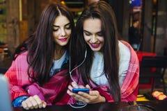 Dwa dziewczyn siedzący słuchanie muzyka z smartphone Obraz Stock
