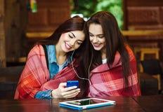 Dwa dziewczyn siedzący słuchanie muzyka z smartphone Fotografia Stock