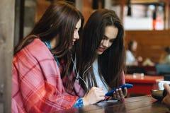 Dwa dziewczyn siedzący słuchanie muzyka z smartphone Fotografia Royalty Free