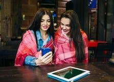 Dwa dziewczyn siedzący słuchanie muzyka z smartphone Obrazy Stock