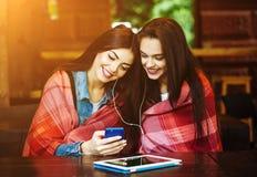 Dwa dziewczyn siedzący słuchanie muzyka z smartphone Obraz Royalty Free
