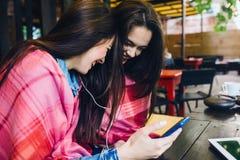 Dwa dziewczyn siedzący słuchanie muzyka z smartphone Zdjęcia Royalty Free