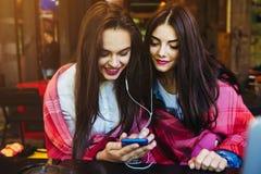 Dwa dziewczyn siedzący słuchanie muzyka z smartphone Obrazy Royalty Free