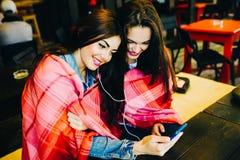 Dwa dziewczyn siedzący słuchanie muzyka z smartphone Zdjęcie Stock