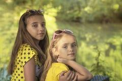 Dwa dziewczyn siedzieć outside na słonecznym dniu Małe siostry w lato lesie zdjęcia royalty free