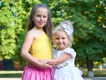 Dwa dziewczyn siostrzany portret, dzieciństwa pojęcie, szczęśliwy dziecko pozuje w miasto parku Fotografia Royalty Free