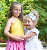 Dwa dziewczyn siostrzany portret, dzieciństwa pojęcie, szczęśliwy dziecko pozuje w miasto parku Zdjęcia Royalty Free