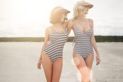 Dwa dziewczyn stojak przy wieczór plażą Zdjęcia Stock