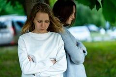 Dwa dziewczyn uczennicy nastolatek w lecie w parku drzewem, Pojęcie bełt, problemy, ansa, malkontenctwo fotografia stock