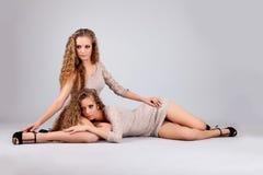 Dwa dziewczyna bliźniaka, odizolowywającego na popielatym tle obraz royalty free