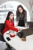 Dwa dziewczyna projektanta pracuj? z laptopem i dokumentacj? przy projektem w eleganckim biurze Projekta tworzenie fotografia royalty free