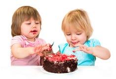 Dwa dziewczynki łasowania mały tort Fotografia Stock