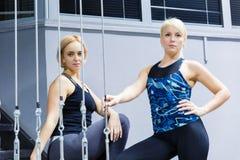 Dwa dziewczyny atlety pozuje przed kamery obsiadaniem na żelaznych schodkach zdjęcia royalty free