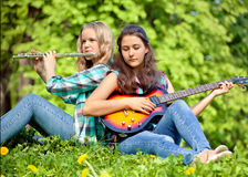 Dwa dziewczyny bawić się gitarę i flet w parku Zdjęcie Royalty Free