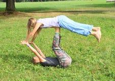 Dwa dziewczyny bawić się joga na łące i ćwiczy Zdjęcia Stock