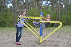 Dwa dziewczyny bawić się na boisku na żółtego metalu przyciąganiu Ja jest wietrzny Zdjęcie Stock
