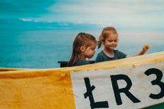 Dwa dziewczyny bawić się w łodzi rybackiej na plaży Zdjęcie Royalty Free