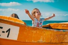 Dwa dziewczyny bawić się w łodzi rybackiej na plaży Zdjęcia Royalty Free