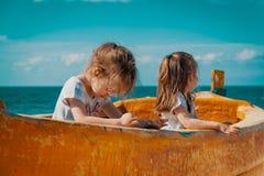 Dwa dziewczyny bawić się w łodzi rybackiej na plaży Obrazy Royalty Free