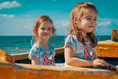 Dwa dziewczyny bawić się w łodzi rybackiej na plaży Obrazy Stock