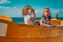 Dwa dziewczyny bawić się w łodzi rybackiej na plaży Fotografia Royalty Free