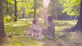 Dwa dziewczyny bawić się w parku na trawie blisko drzewa zdjęcie wideo