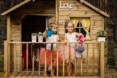 Dwa dziewczyny bawić się z podlewanie puszką w drzewnym domu Fotografia Stock