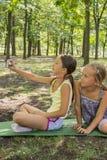 Dwa dziewczyny bierze fotografię w parku Dziewczyny w parku robią selfies dwa beautifu nastolatka dziewczyny robią selfie w parku fotografia royalty free