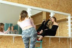 Dwa dziewczyny biorą obrazki each inny w przebieralni jaskrawy pokój zdjęcia royalty free
