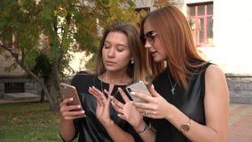Dwa dziewczyny dziewczyny chodzą puszek i opowiadają ulica używać smartphone zbiory