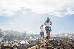 Dwa dziewczyny chodzi wokoło śmieciarskiej góry zdjęcia stock
