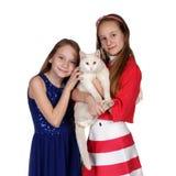 Dwa dziewczyny ściska kota Zdjęcia Royalty Free