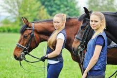 Dwa dziewczyny - dressage jeźdzowie z koniami Zdjęcia Royalty Free