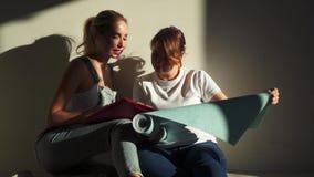 Dwa dziewczyny dyskutuje tapety dla ich mieszkania i wybiera przy budow? zbiory