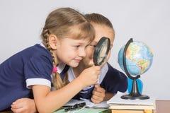 Dwa dziewczyny dziewczyny patrzeje kulę ziemską przez powiększać - szkło Zdjęcie Stock