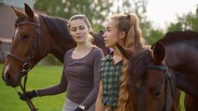 Dwa dziewczyny iść blisko koni zbiory