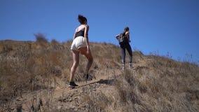 Dwa dziewczyny iść ciężkimi, jeden są w activewear, po drugie są w, skrótach i wierzchołku, przyjaciele wycieczkuje w górę wpólni zbiory wideo