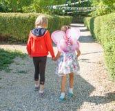 Dwa dziewczyny iść na ścieżce i trzyma ręki fotografia stock