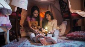 Dwa dziewczyny jest ubranym piżamy czytelniczą książkę w domu robić koc przy nocą zdjęcie wideo