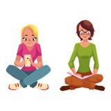 Dwa dziewczyny jest usytuowanym krzyżować nogi, czytelnicza książka, używać telefon komórkowego Obrazy Stock