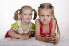 Dwa dziewczyny kłaść opierać na jego rękach i patrzeć w ramie Zdjęcie Royalty Free