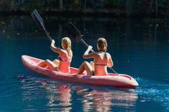 Dwa dziewczyny kayaking na błękitnym jeziorze, Laguna Dudu obrazy royalty free