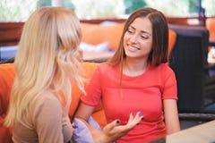 Dwa dziewczyny komunikuje w kawiarni obraz royalty free