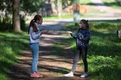 Dwa dziewczyny lub dziewczyny opowiadają emocjonalnie outdoors Zdjęcia Royalty Free