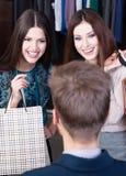 Dwa dziewczyny mówją sprzedawca Zdjęcie Stock