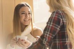 Dwa dziewczyny ma zabawę podczas gdy pijący kawę Obrazy Royalty Free