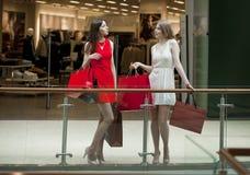 Dwa dziewczyny na zakupy chodzą na centrum handlowym z torbami Zdjęcia Royalty Free