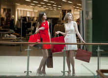 Dwa dziewczyny na zakupy chodzą na centrum handlowym z torbami Fotografia Royalty Free