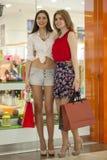 Dwa dziewczyny na zakupy chodzą na centrum handlowym z torbami Zdjęcie Royalty Free