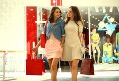 Dwa dziewczyny na zakupy chodzą na centrum handlowym z torbami Fotografia Stock